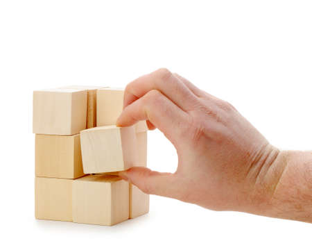 yellow block: The hand establishes a wooden cube. It is isolated on a white background