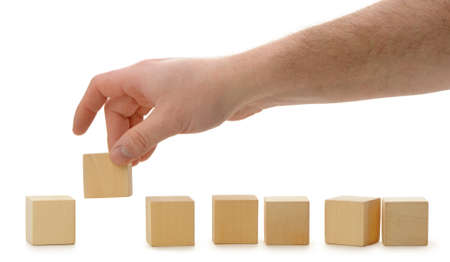 building activity: The hand establishes a wooden cube in row. It is isolated on a white background Stock Photo