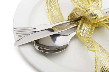 dinnerware: Spoon, fork and a knife tied up celebratory ribbon. Lie on a plate