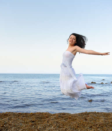 The young woman jumps on seacoast. A picturesque landscape photo