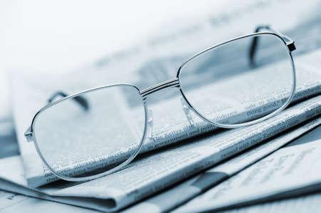 actuality: Occhiali da vista si trovano su un mucchio di tonica newspapers.Blue. Una foto da vicino. Messa a fuoco selettiva Archivio Fotografico