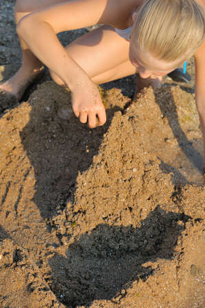 The girl builds sand castle. Sits on seacoast photo