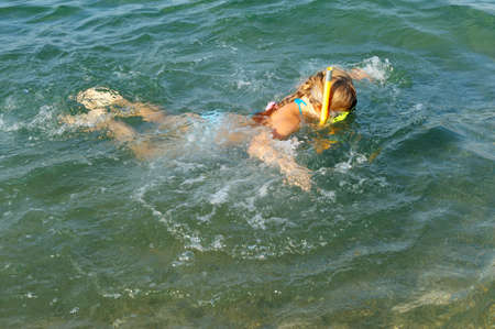 The girl floats under water. In a mask, flippers and with a snorkel photo