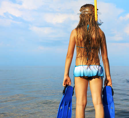 only girls: The girl on seacoast looks in a distance. In a mask, flippers and with a snorkel