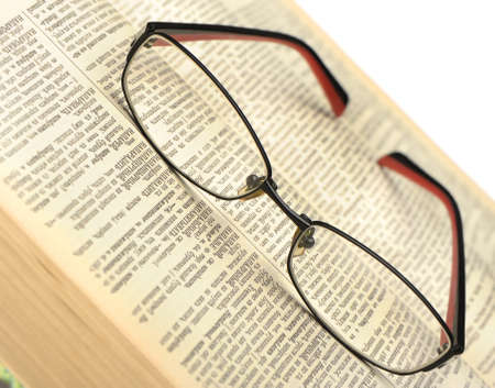 Eyeglasses on the old thick book. A photo close up