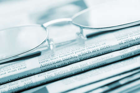 broadsheet newspaper: Eyeglasses lie on a pile of newspapers.Blue toned. A photo close up. Selective focus