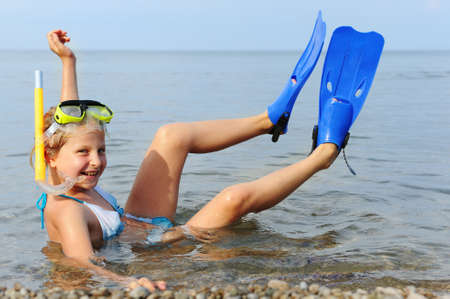 The girl on seacoast. In a mask, flippers and with a snorkel photo