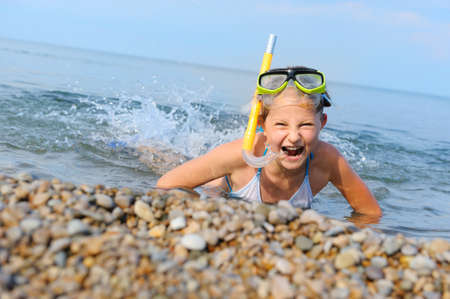 The girl on seacoast flounders about in water. In a mask, flippers and with a snorkel photo