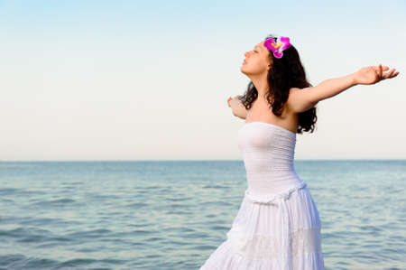 The woman in a white sundress on seacoast with open hands. A picturesque landscape Stock Photo - 12543340