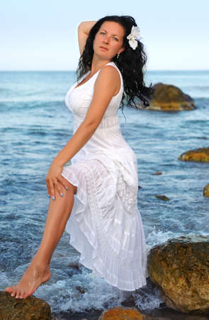 sundress: The woman in a white sundress on seacoast. A picturesque landscape Stock Photo