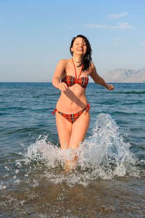 The joyful woman runs on sea water photo