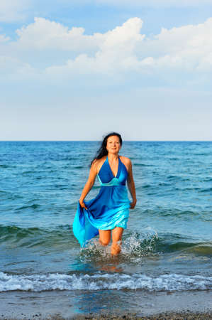 The attractive woman exit the sea. A dark blue dress photo