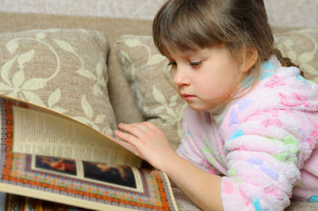 The little girl reads the book lying on a sofa. A house room photo