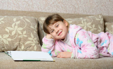 The little girl reads the book lying on a sofa. A house room Stock Photo - 12543595