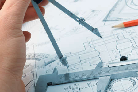 industrial drawing: The plan industrial details and a hand with divider. A photo closeup. Blue toning