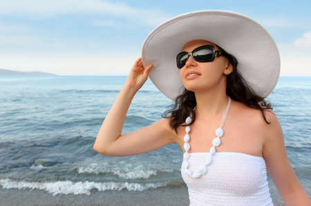 The woman on seacoast. In sun glasses, a sundress, a hat. photo