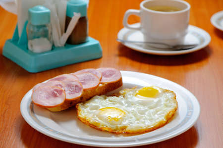 Breakfast. Fried eggs, a sandwich and tea photo