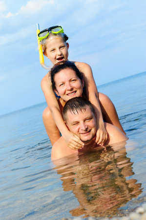 Happy family in the sea. Mum, the father and the daughter photo