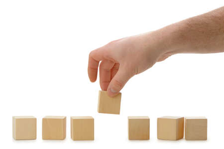 wood blocks: The hand establishes a wooden cube in row. It is isolated on a white background Stock Photo