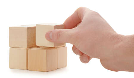 The hand establishes a wooden cube. It is isolated on a white background