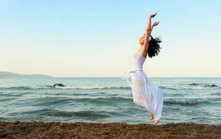 outstretched arms: The young woman jumps on seacoast. A picturesque landscape
