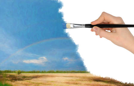 saturate: The hand with a brush draws a landscape.The blue sky, field and rainbow