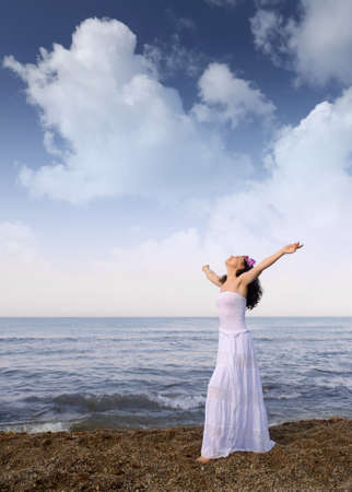 The woman in a white sundress on seacoast with open hands. Cloud sky Stock Photo - 12701235