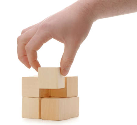 wood blocks: The hand establishes a wooden cube. It is isolated on a white background