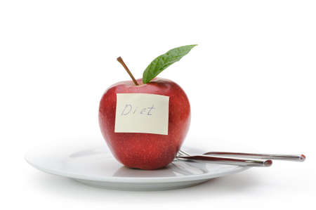 Apple with a paper note. Inscriptions on the notes diet. Fruit on a plate with a knife and fork isolated on white background photo