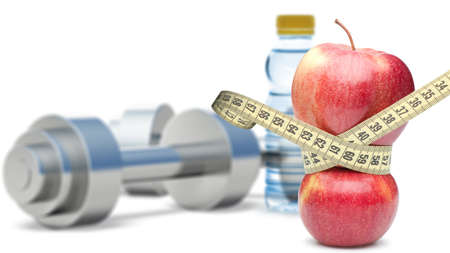 Dumbbells with an apple and measuring type. Dumbbells blured on a background. It is isolated on a white background photo