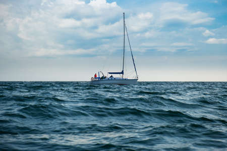 A yacht in a stormy sea. A boat lowered the sails and unrecognisable people photo