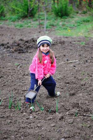 The little girl works in the garden. Autumn Stock Photo - 13099790