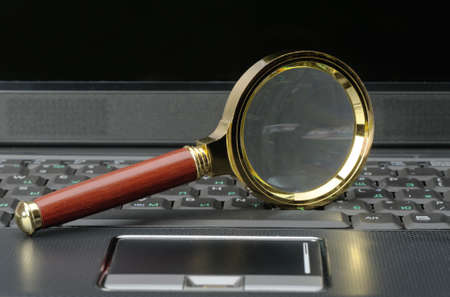Magnifying glass and a laptop. The concept of search photo