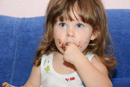 The little girl eats a cake. Funny picture photo
