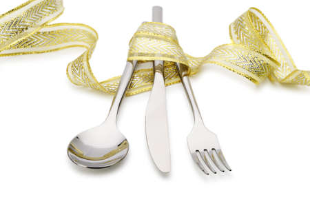 Spoon, fork and a knife tied up celebratory ribbon. It is isolated on a white background photo