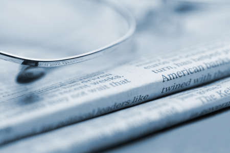 Eyeglasses lie on a pile of newspapers.Blue toned. A photo close up. Selective focus photo