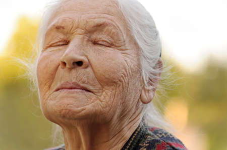 The elderly woman with closed eyes. A photo outdoors photo