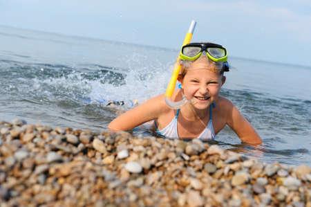 flippers: La chica de costa marítima sobre lenguados en el agua. En una máscara, aletas y snorkel con un