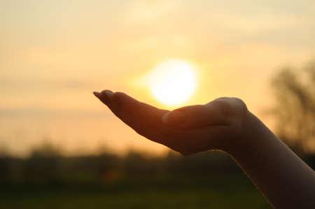 La puesta de sol en la mano. La fotografía abstracta en la iluminación de fondo Foto de archivo