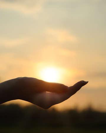 mano de dios: La puesta de sol en la mano. La fotograf�a abstracta en la iluminaci�n de fondo Foto de archivo