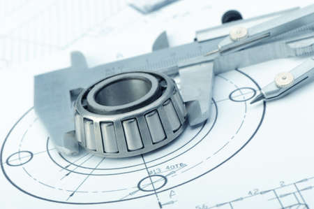 manufacturing occupation: The plan industrial details, a protractor, caliper, divider and bearing. A photo closeup. Blue toning