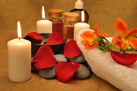 body oil: Object for the spa. Candles burning, Pebble, Lily, liquid soap, a bottle with oil, bowl with the petals of roses in water, and another.