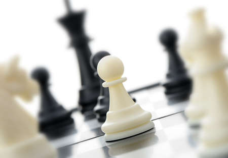 chessboard: White chess pawn. In an environment of other figures. Selective focus