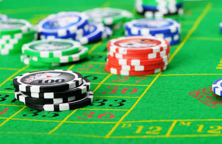 Gaming chips on the green cloth casino photo