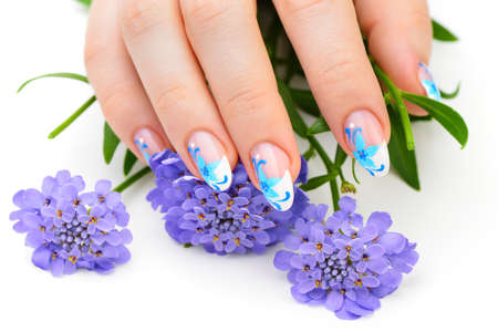 Nail art. Female nails with figure of petal blue color closeup and flower Stock Photo - 14390105