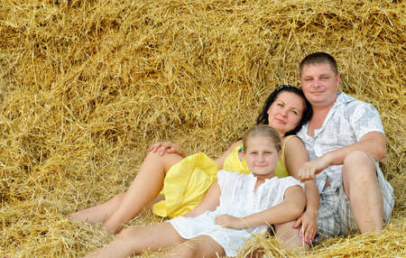 A young family, father, mother and daughter. On the background of the large stack of hay Stock Photo - 14649533