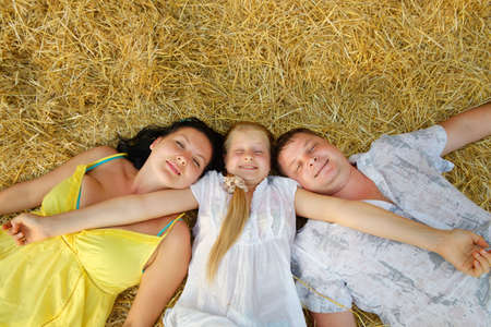 A young family, father, mother and daughter. Lie on hay Stock Photo - 14649530
