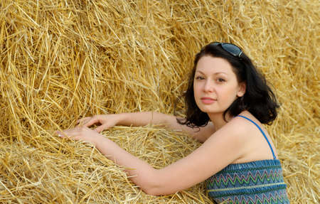 A young attractive woman on the background of the large stack of hay photo
