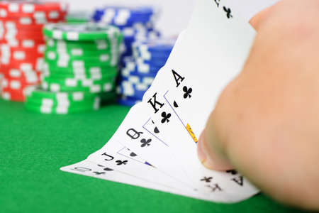 Gaming chips and cards on the green cloth. A winning combination in a poker Royal Flush photo