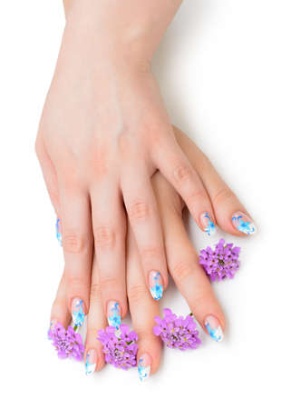 Nail art. Female nails with figure of petal blue color closeup and flower photo